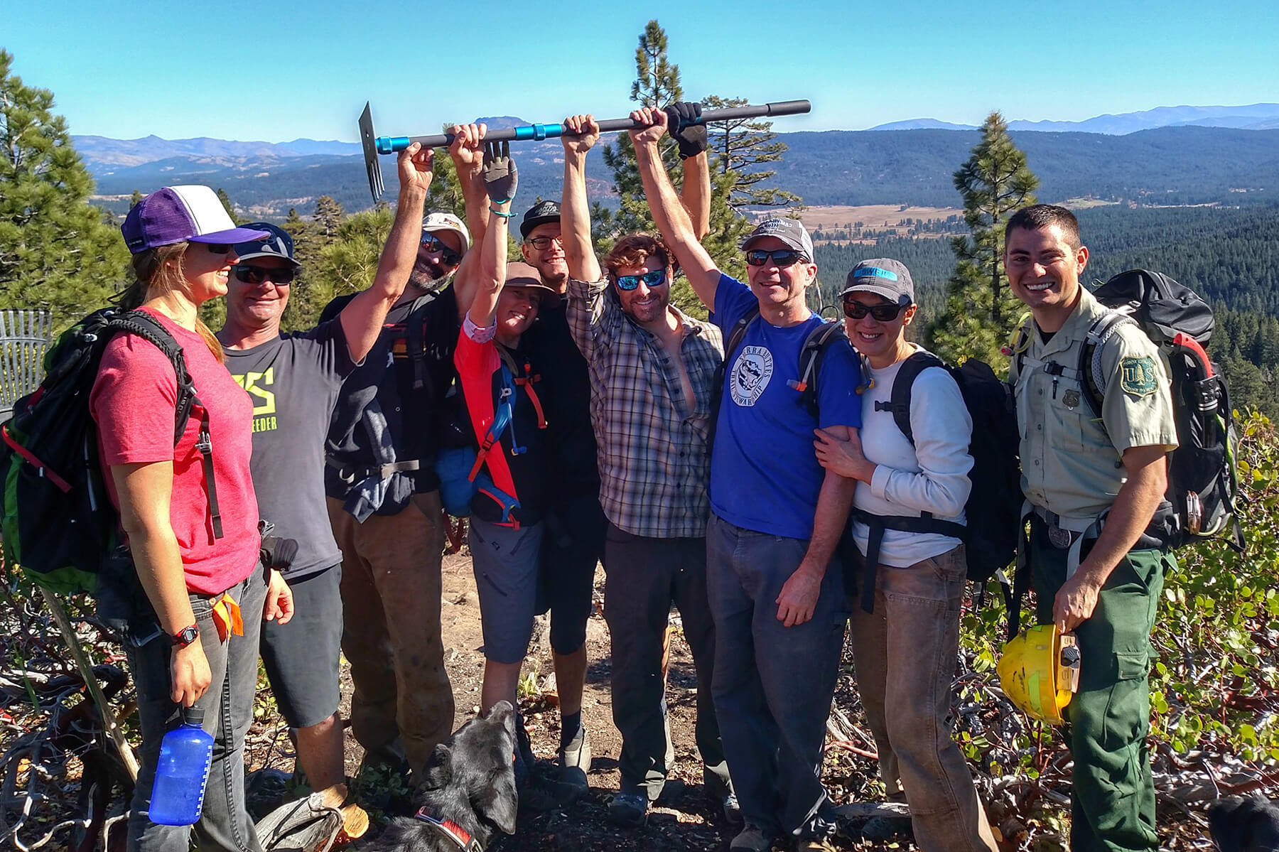 Trailworkers holding trail tool in celebration