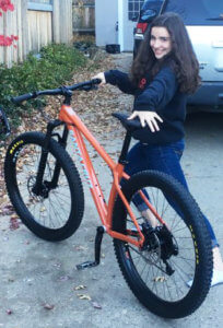 Emma smiling with her Santa Cruz Chameleon bike.