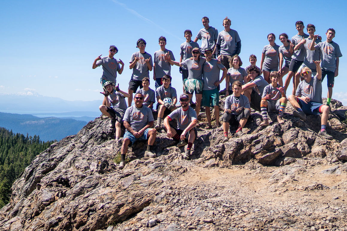 NorCal Group of kids on rocks of Mt. Hough with mountains and lakes in background
