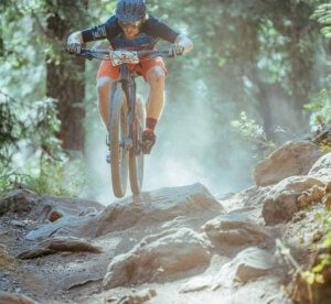 Mountain bike racer flying over rocks