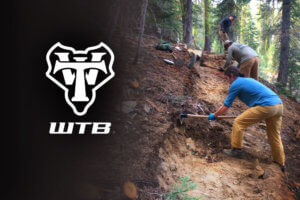 WTB logo and workers on trail