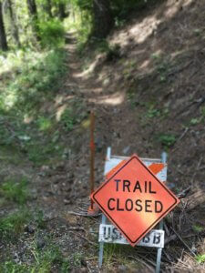 Trail closed sign on trail